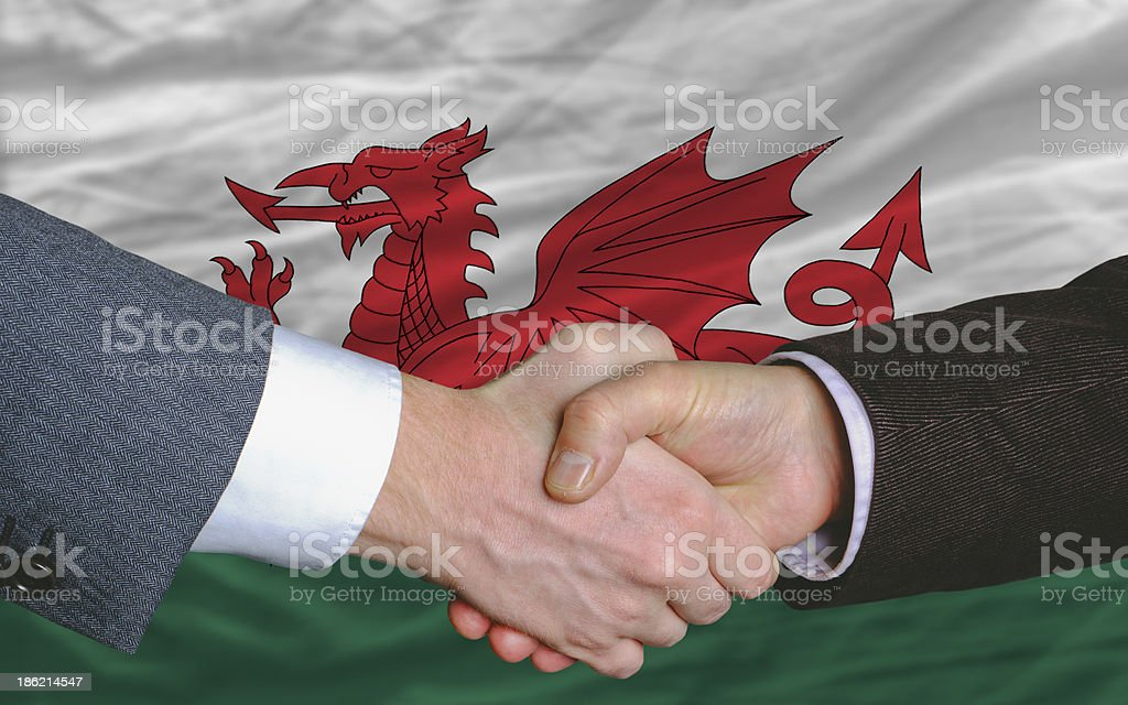 businessmen handshake after good deal in front of wales flag royalty-free stock photo