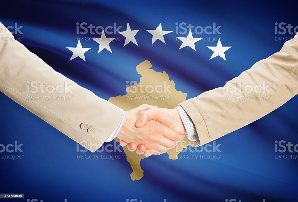 Businessmen handshake with flag on background - Kosovo stock photo