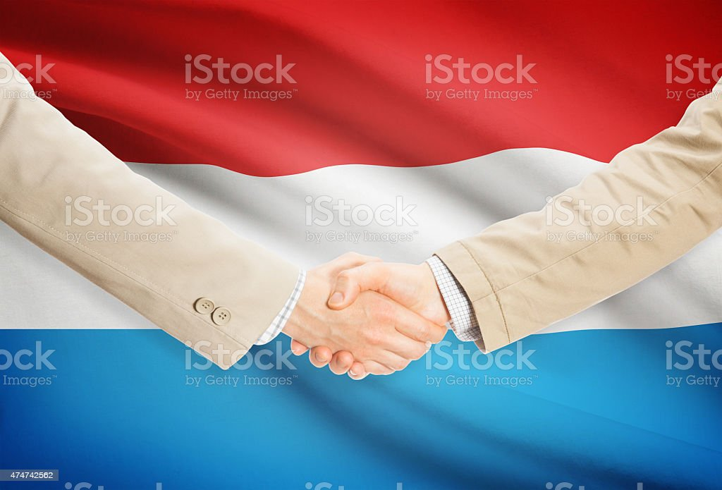 Businessmen handshake with flag on background - Luxembourg stock photo