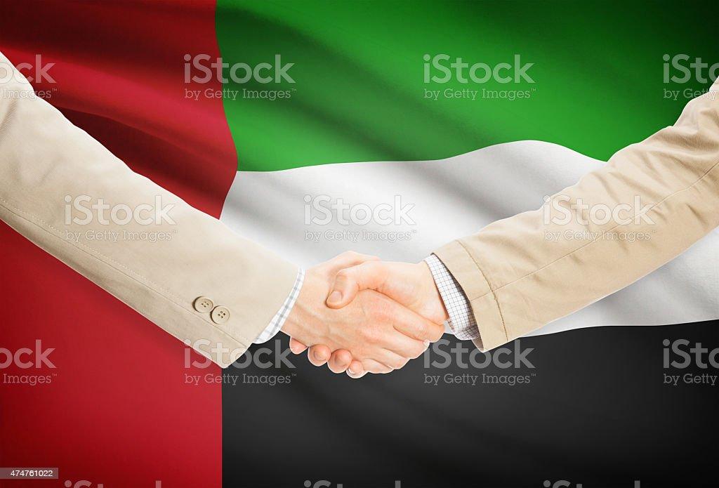 Businessmen handshake with flag on background - United Arab Emirates stock photo