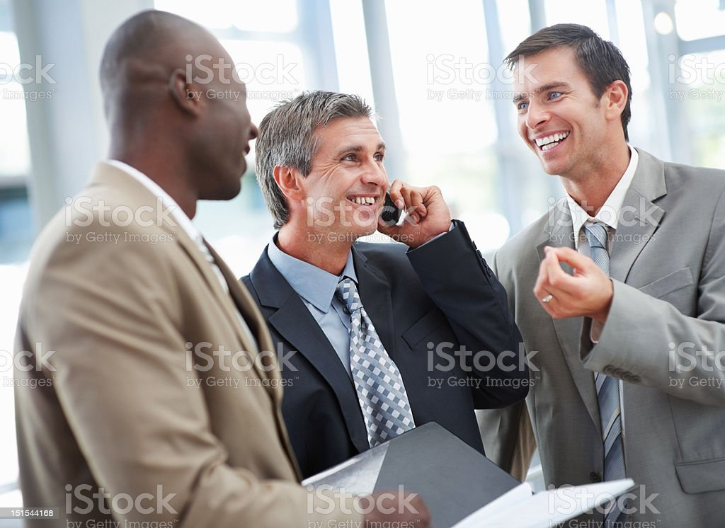 Businessmen having fun while colleague talking on cellphone royalty-free stock photo
