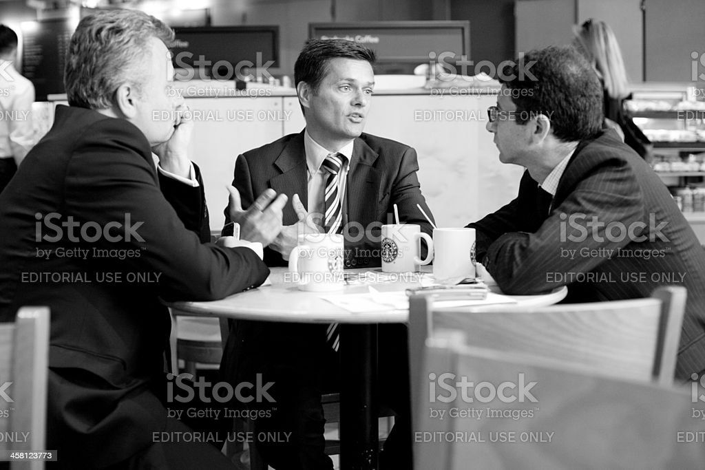 Businessmen having serious meeting at starbucks royalty-free stock photo