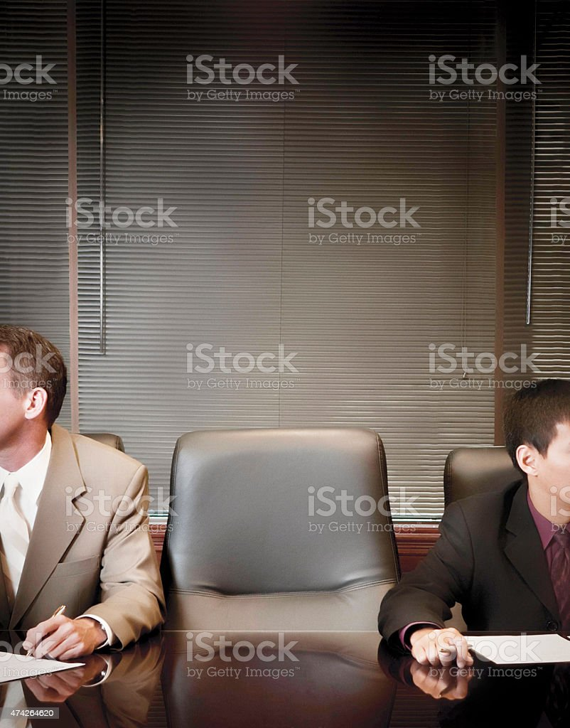 Businessmen in boardroom with empty chair. stock photo
