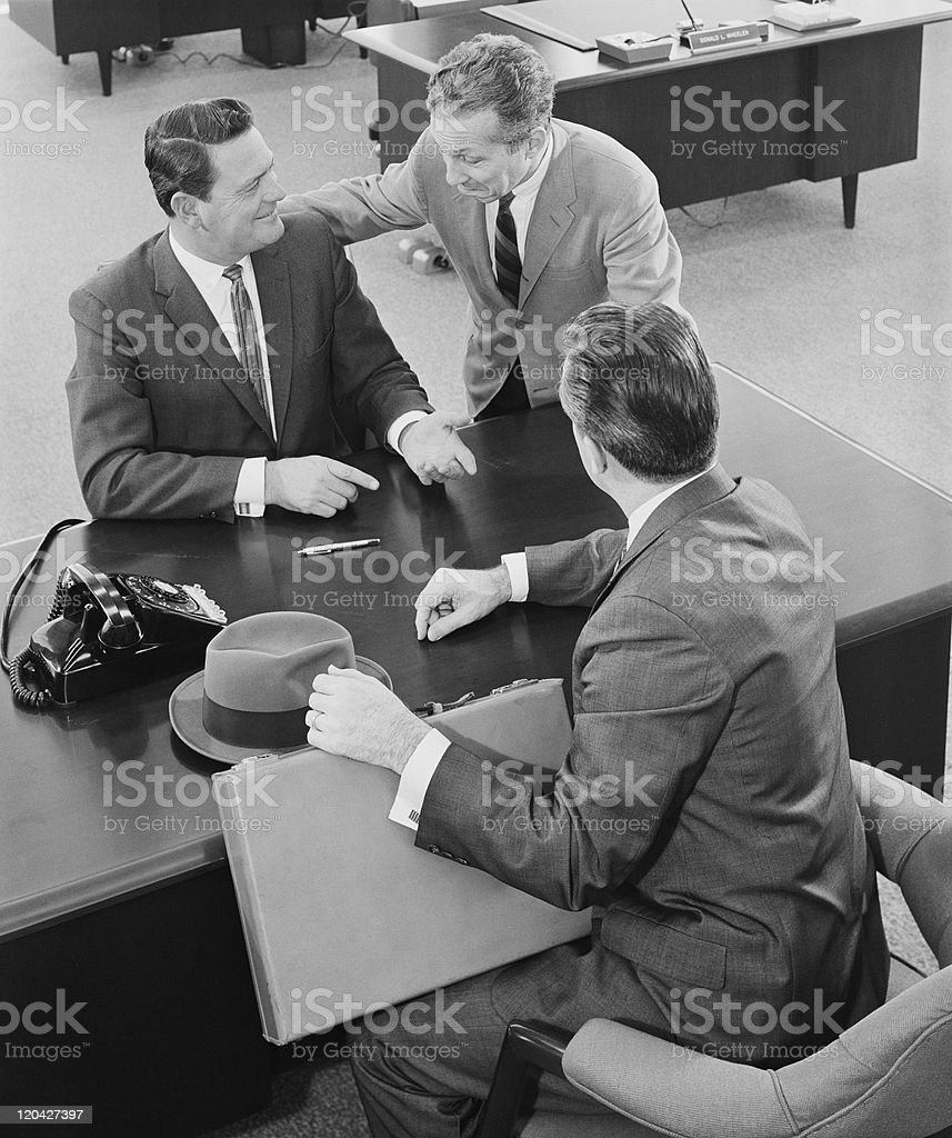 Businessmen in discussion at desk in office stock photo
