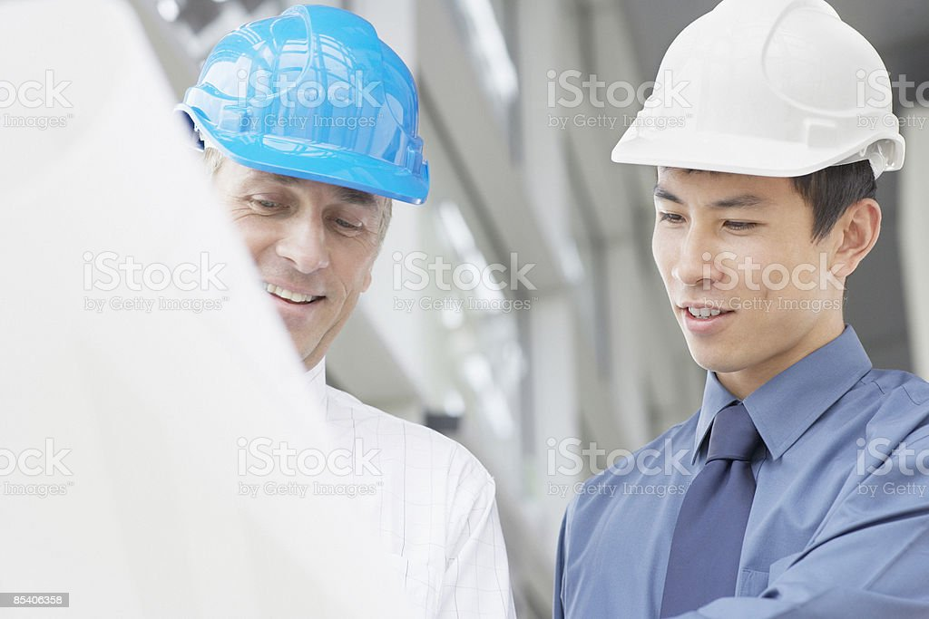 Businessmen in hard-hats looking at blueprints royalty-free stock photo
