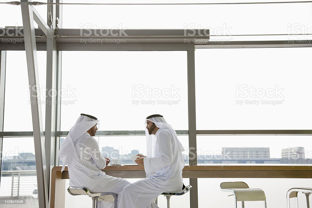 Businessmen in kaffiyehs talking at table in window stock photo