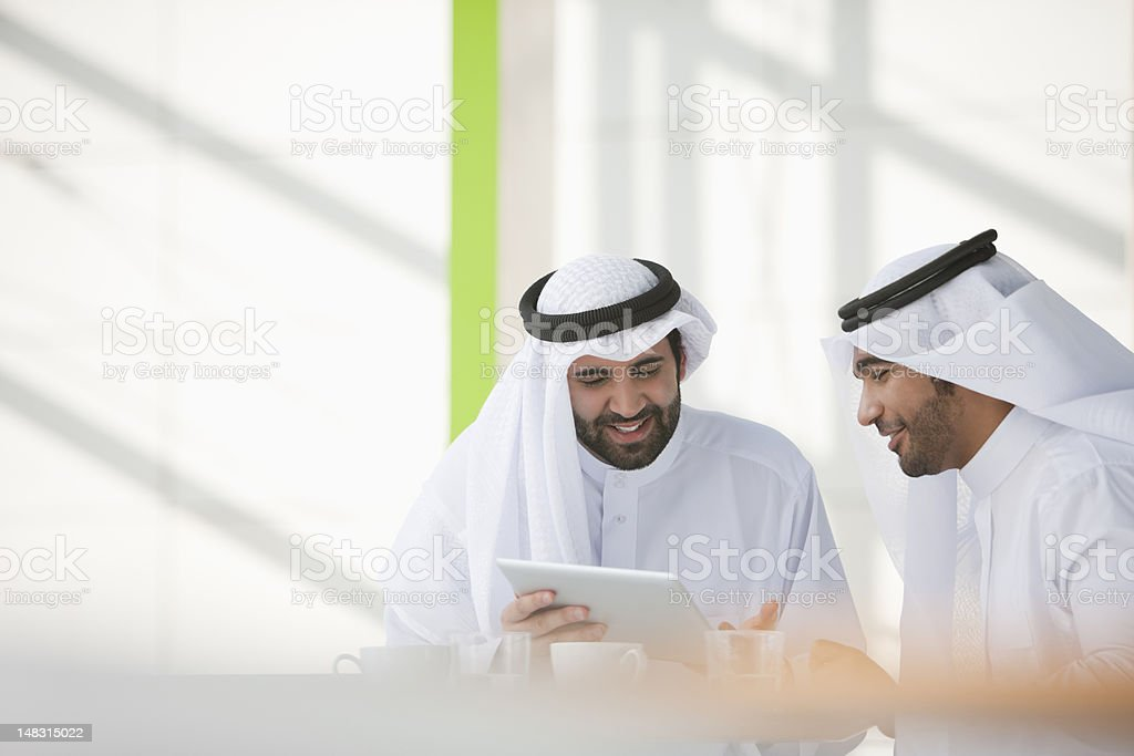 Businessmen in kaffiyehs using digital tablet stock photo
