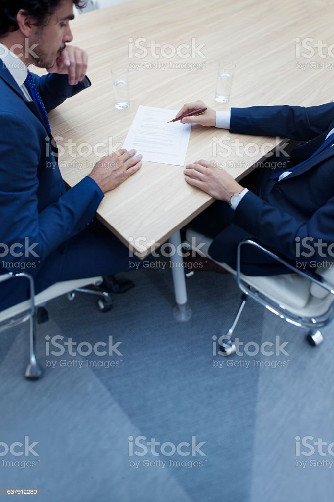 Businessmen in negotiation at meeting table stock photo