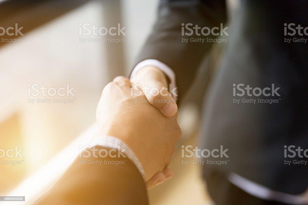 businessmen in suit shaking hands beside window - stock photo