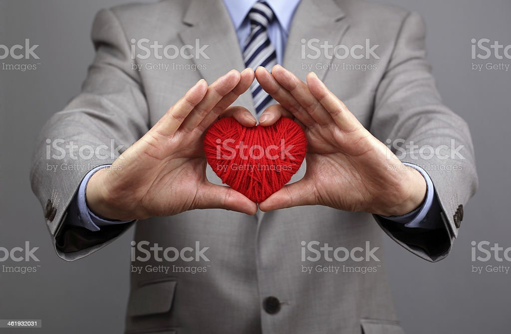 Businessmen is holding out a red heart stock photo