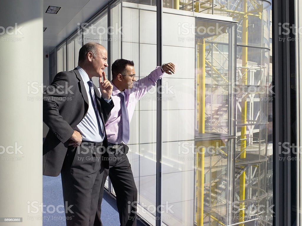 Businessmen looking through window royalty-free stock photo