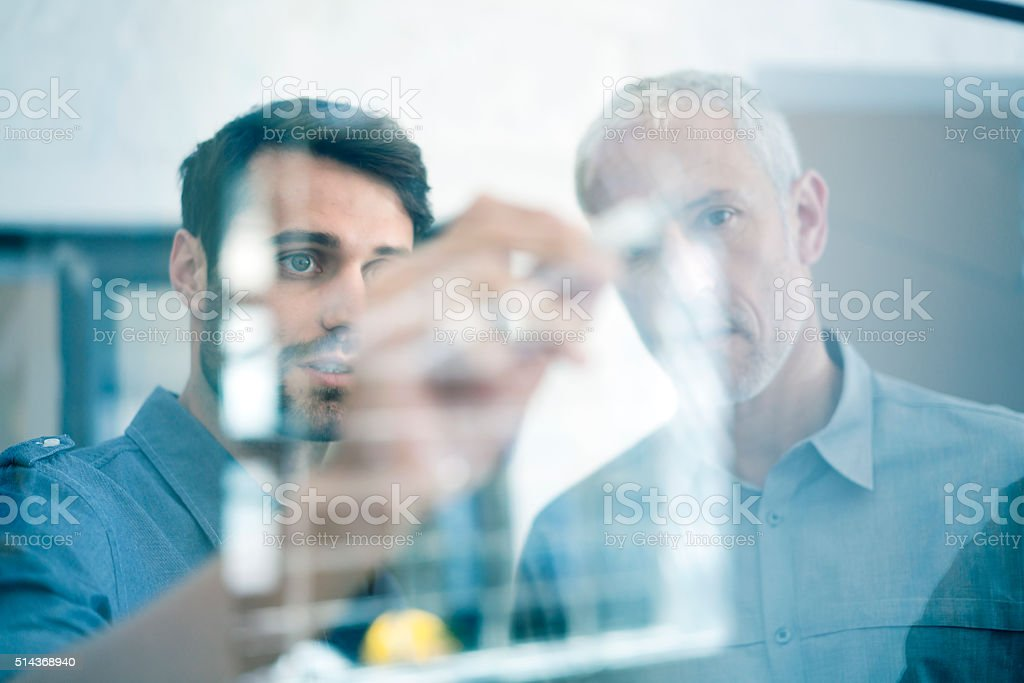 Businessmen making plan on glass wall in office stock photo
