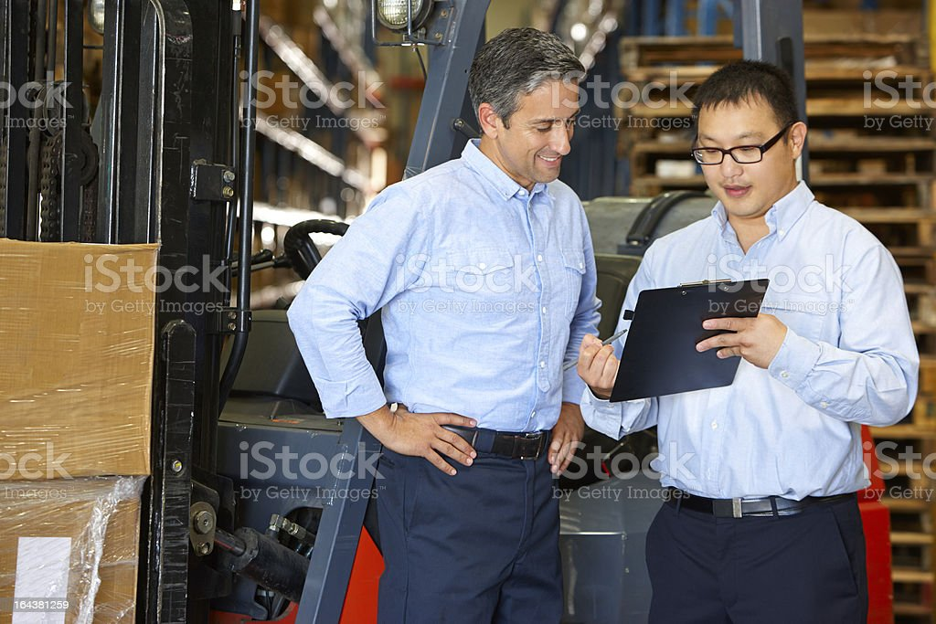 Businessmen Meeting By Fork Lift Truck In Warehouse stock photo