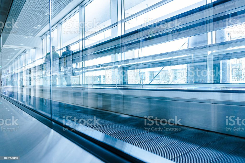 Businessmen moving on escalator in modern hall interior, office building royalty-free stock photo