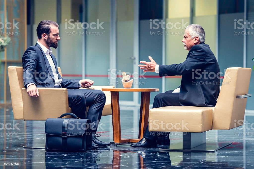 Businessmen negotiating in a modern office lobby stock photo
