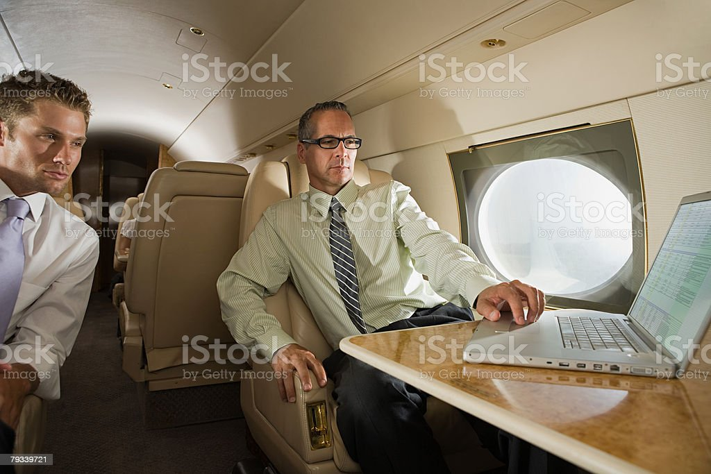 Businessmen on jet with laptop royalty-free stock photo