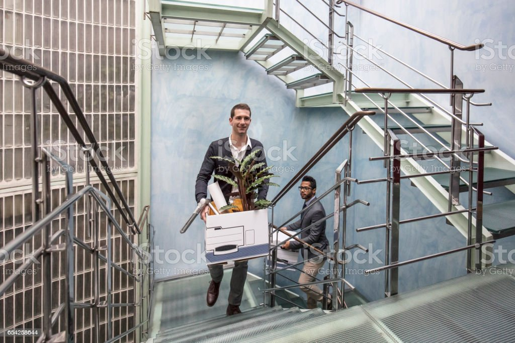 Businessmen on steps with belongings in new office stock photo
