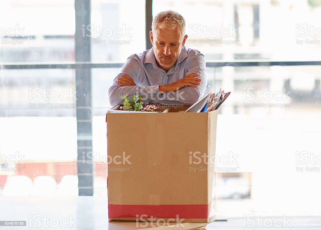 Businessmen packing his belongings away after being fired stock photo