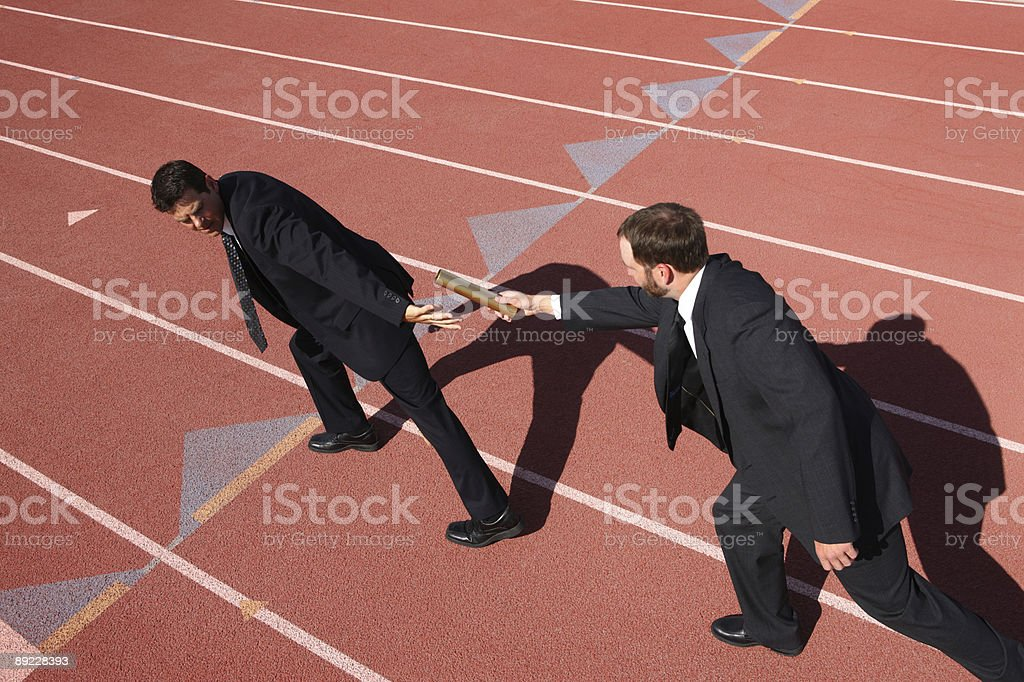 Businessmen passing the baton stock photo