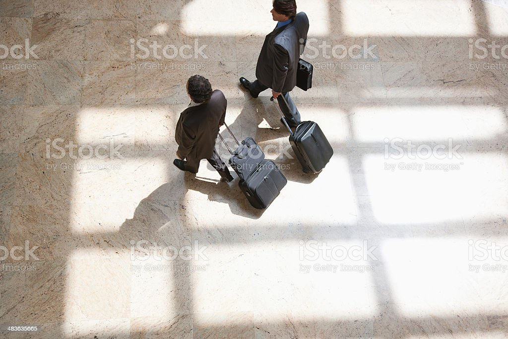 Businessmen pulling rolling suitcases stock photo