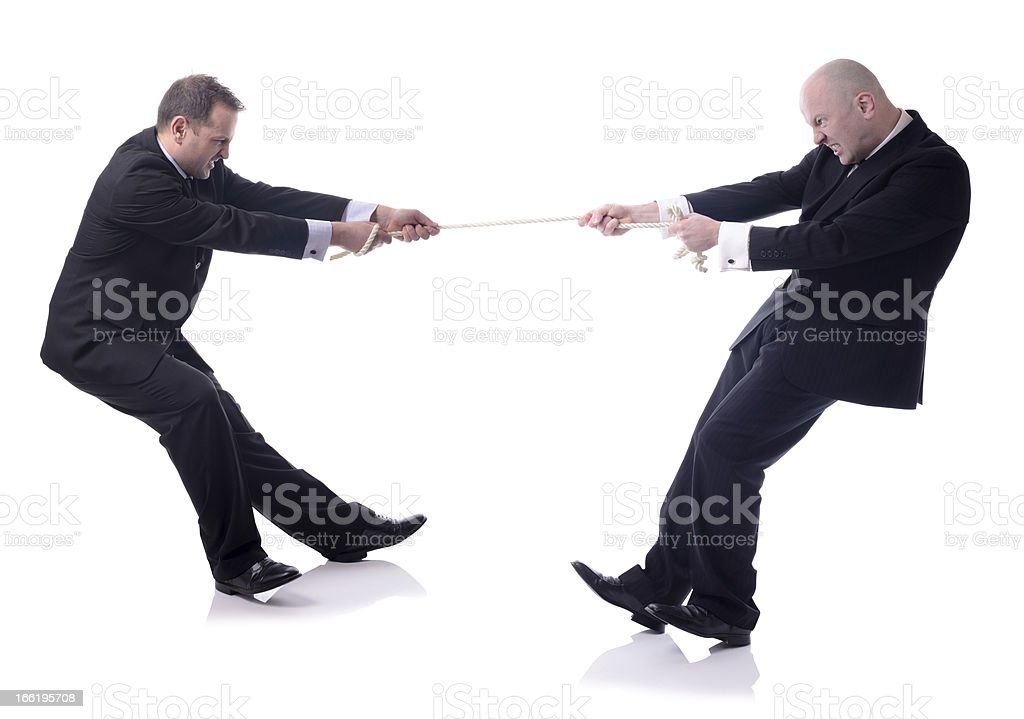 Businessmen pulling the rope on tug of war stock photo