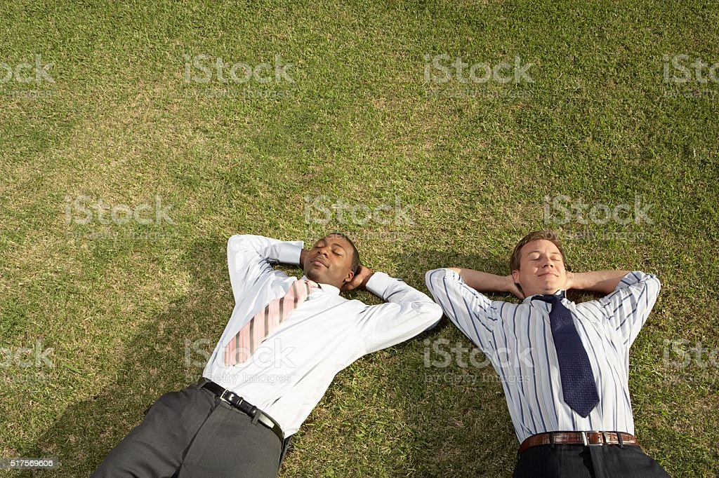 Businessmen relaxing on the grass stock photo