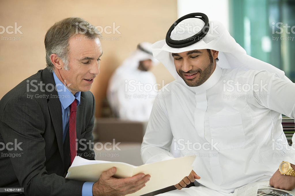 Businessmen reviewing paperwork in meeting stock photo