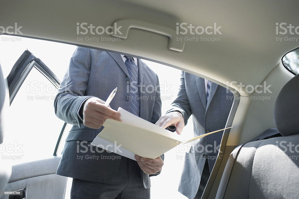 Businessmen reviewing paperwork near car royalty-free stock photo