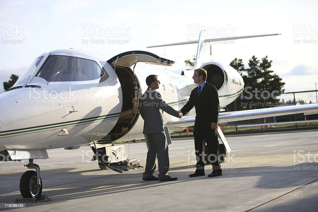 Businessmen shake hands by corporate jet royalty-free stock photo