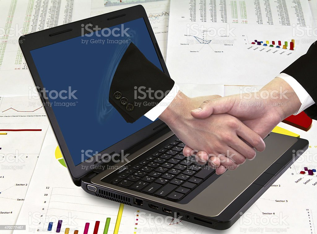 Businessmen shake hands from laptop on financial Graphs stock photo