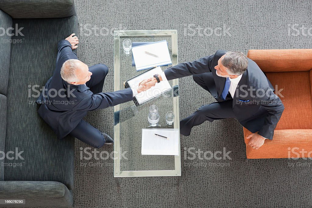 Businessmen shaking hands across coffee table in lobby royalty-free stock photo