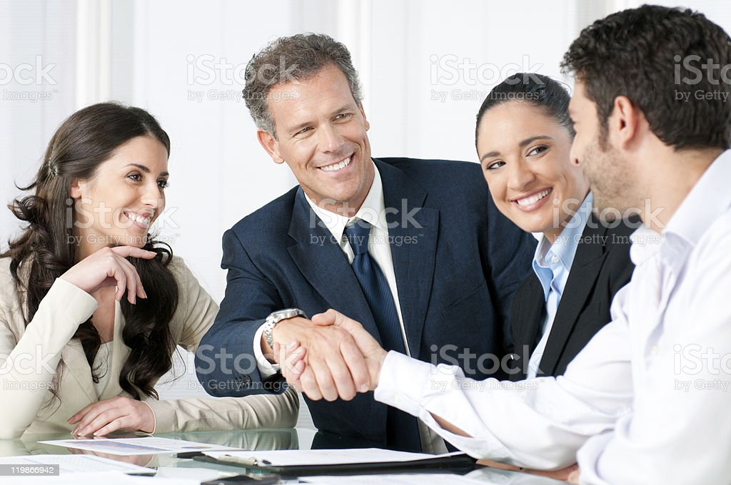 Businessmen shaking hands as colleagues smile stock photo
