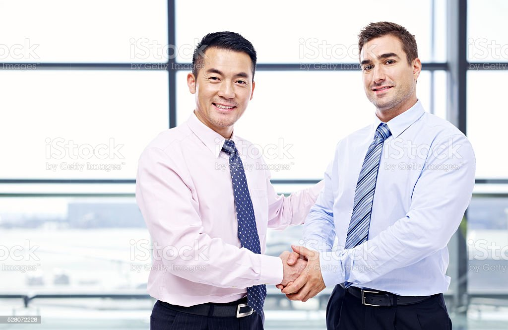 businessmen shaking hands at airport stock photo