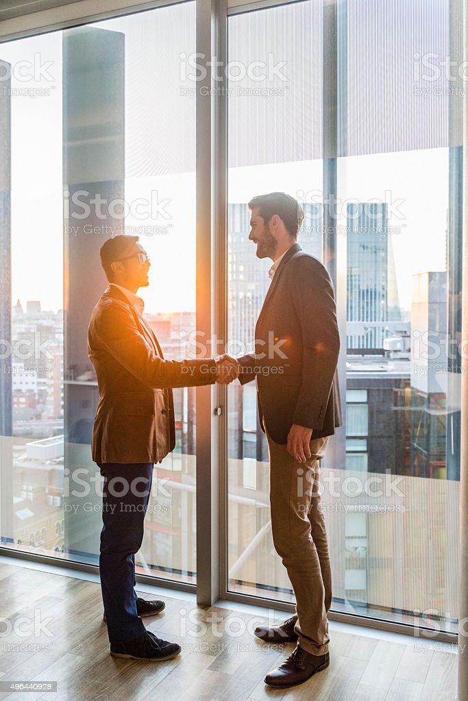Businessmen shaking hands by modern office window stock photo