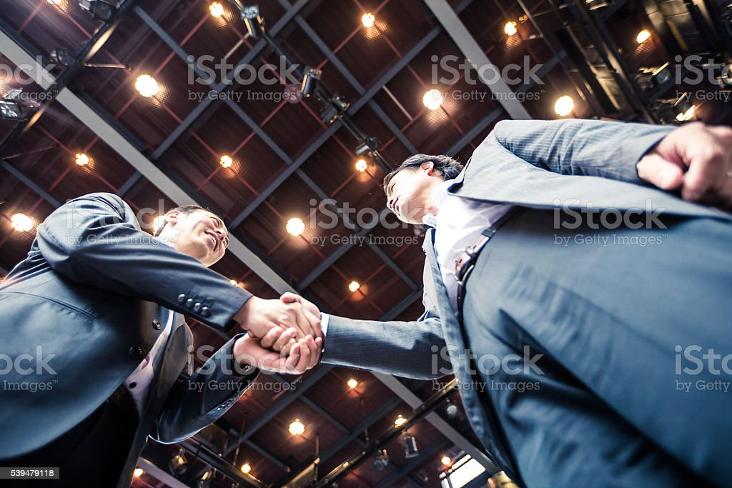 Businessmen shaking hands in agreement over a successful acquisition. stock photo