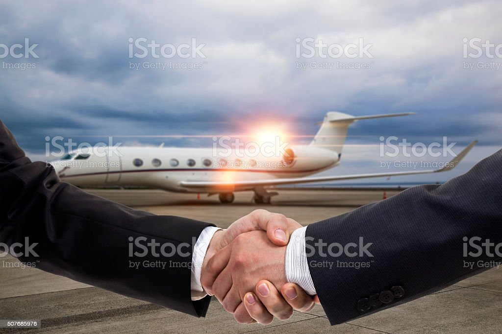 Businessmen shaking hands in front of private jet stock photo