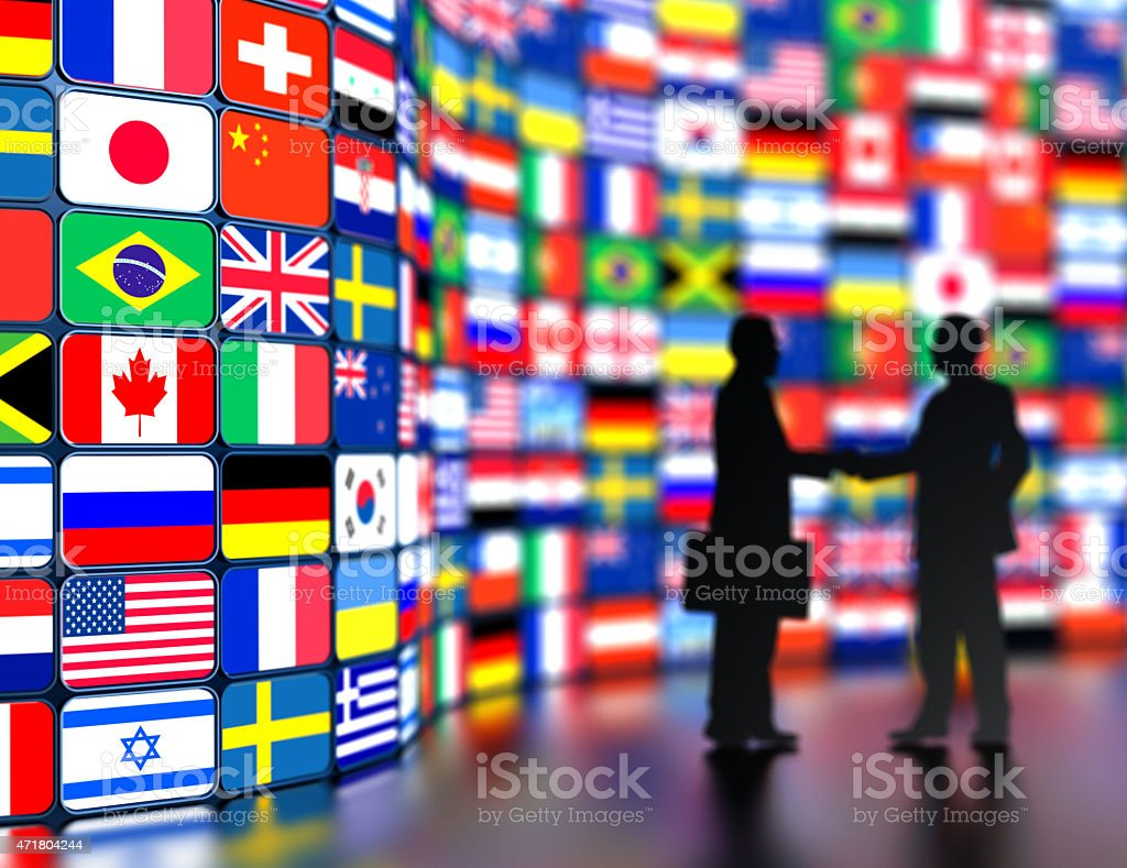Businessmen shaking hands in front of the world flags stock photo