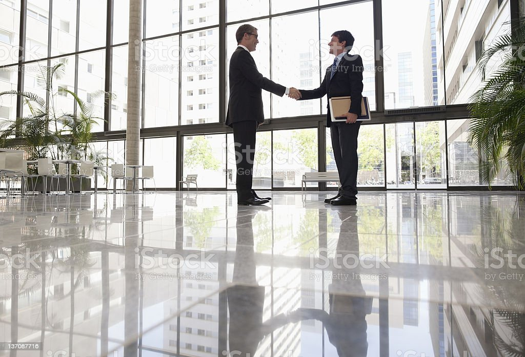 Businessmen shaking hands in office lobby royalty-free stock photo