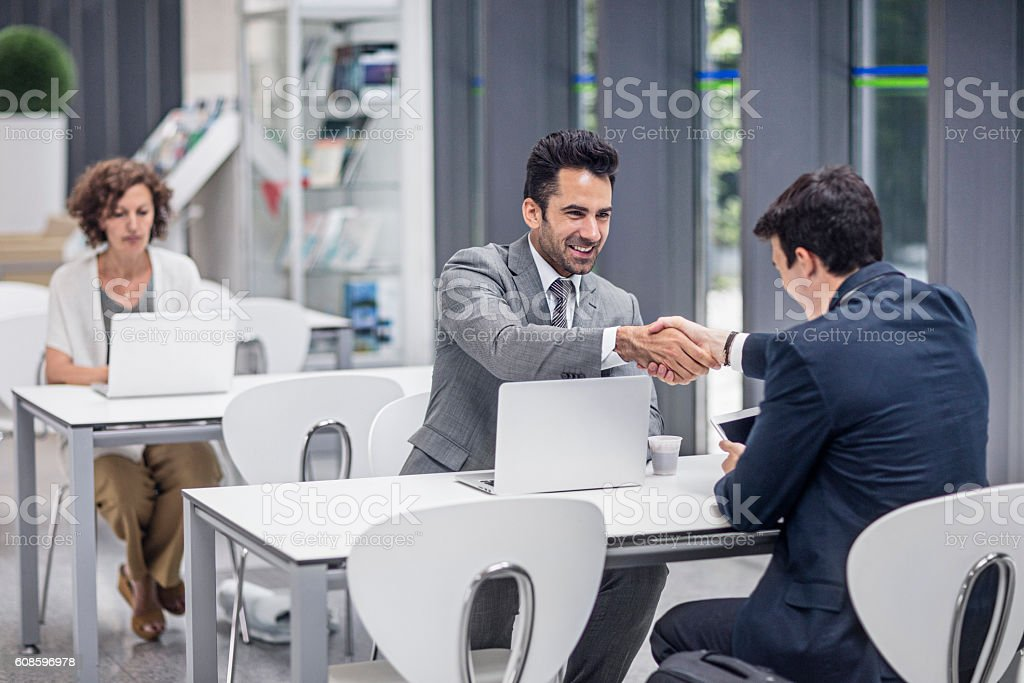 Businessmen shaking hands in the airport stock photo