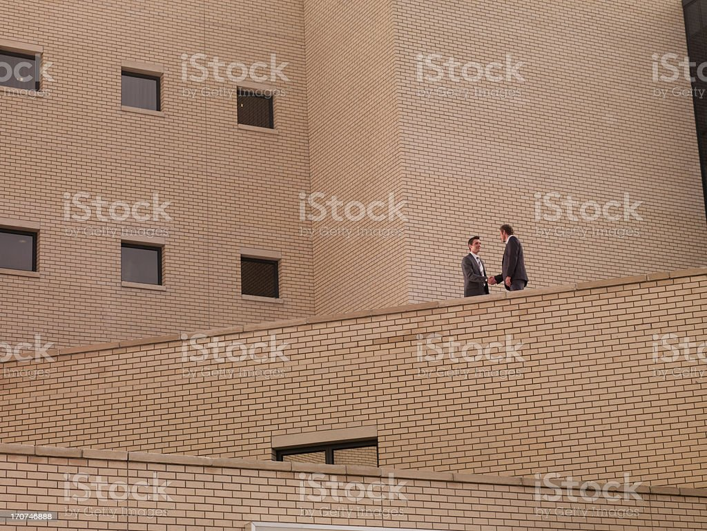 Businessmen shaking hands on balcony royalty-free stock photo