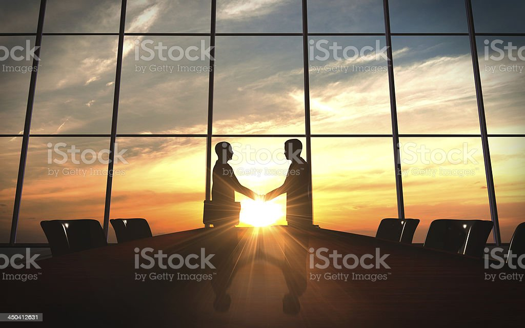 Businessmen shaking hands silhouetted in sunset stock photo