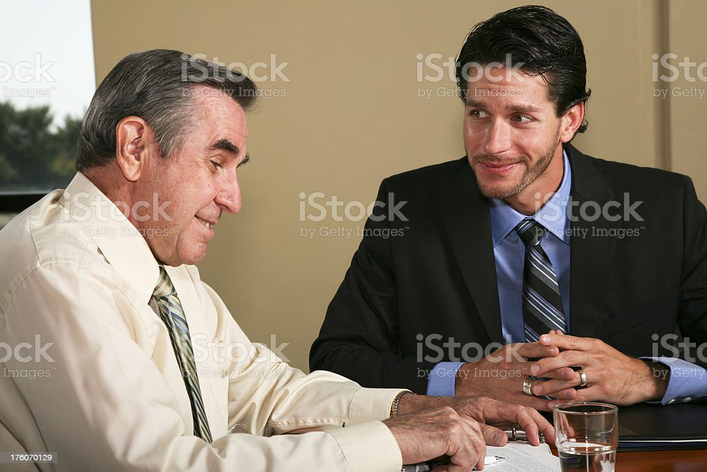 Businessmen Smiling While Looking Over Documents royalty-free stock photo