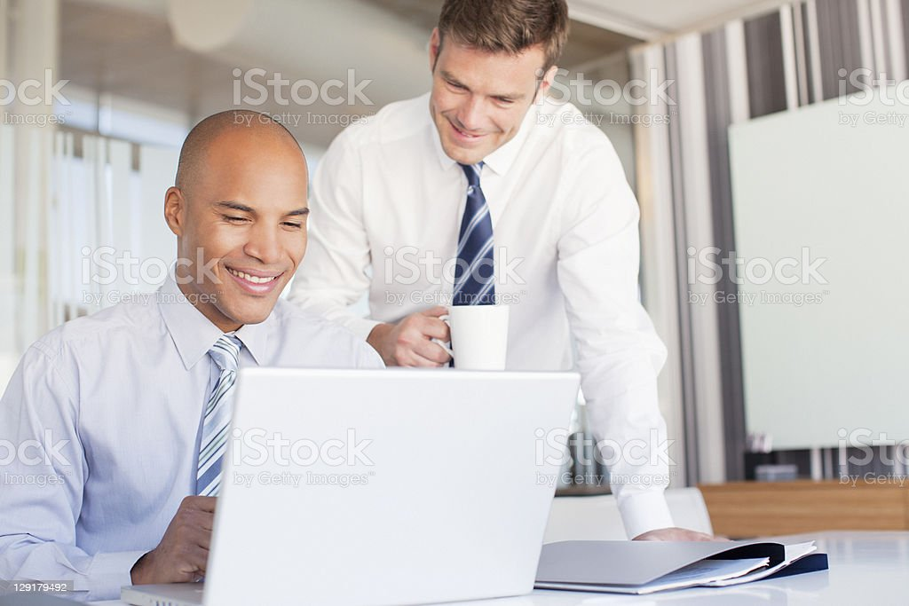 Businessmen smiling while using laptop royalty-free stock photo