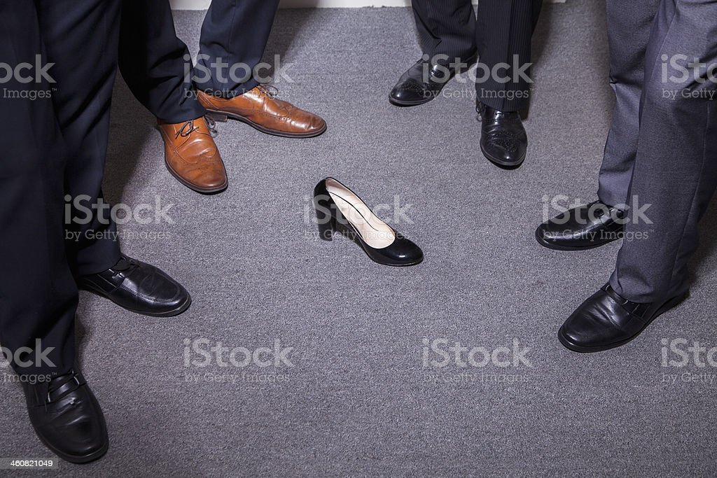 Businessmen standing around a woman's high heel stock photo