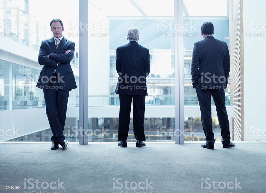 Businessmen standing near glass wall in office stock photo