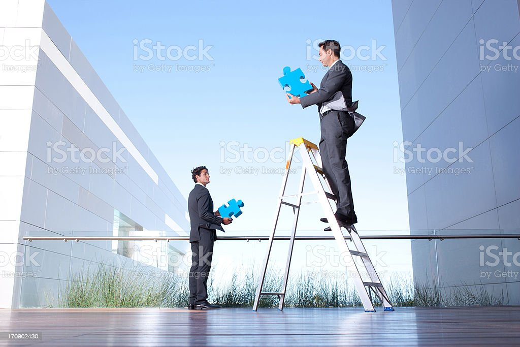 Businessmen standing on balcony holding jigsaw puzzle pieces royalty-free stock photo