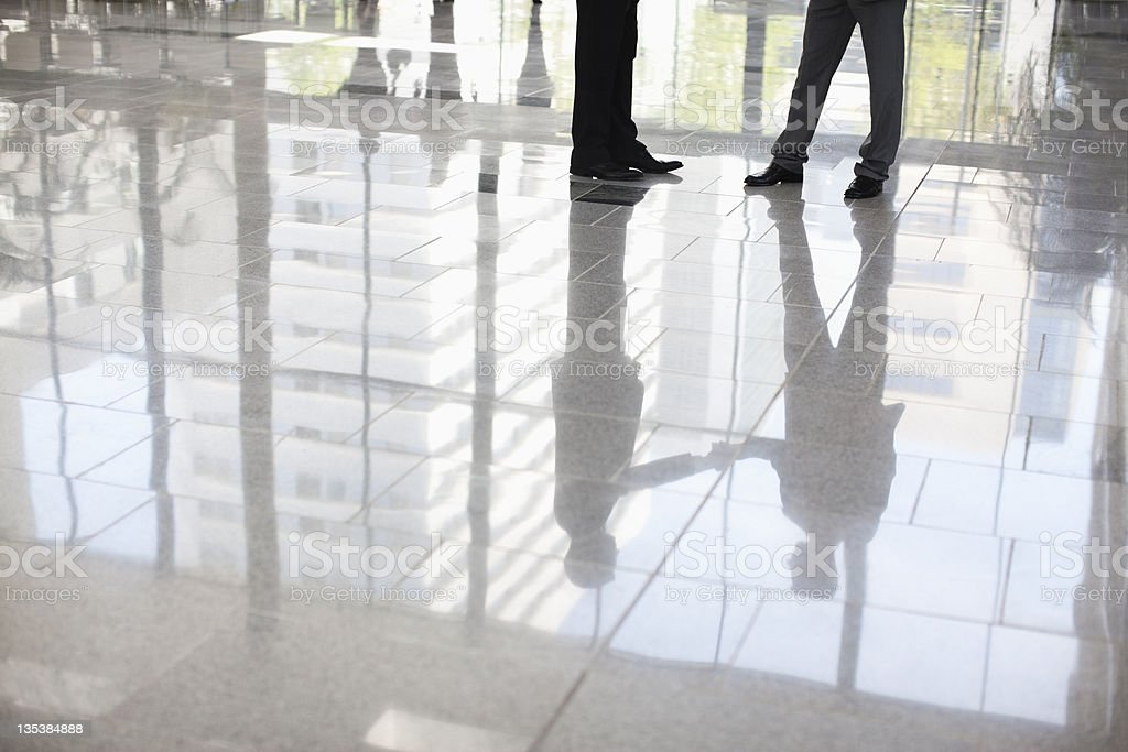 Businessmen standing together in lobby royalty-free stock photo