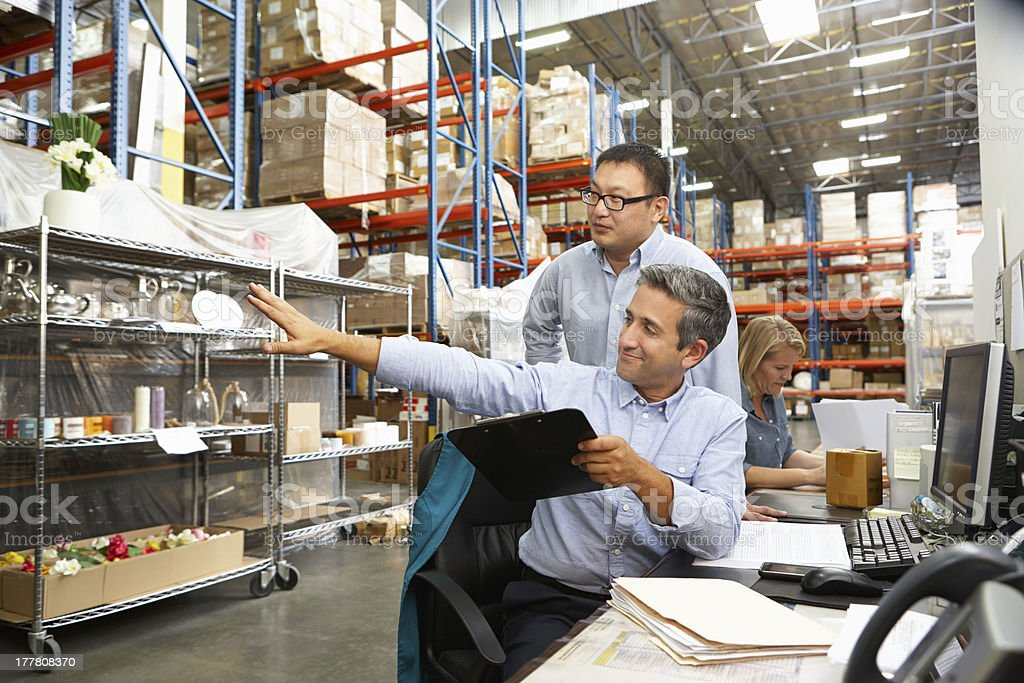2 businessmen staring at some warehouse racking stock photo