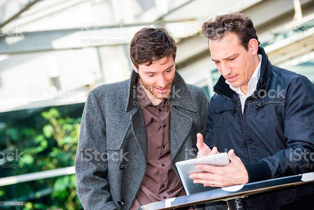 Businessmen Surfing the Net on Digital Tablet in Sidewalk Cafe royalty-free stock photo