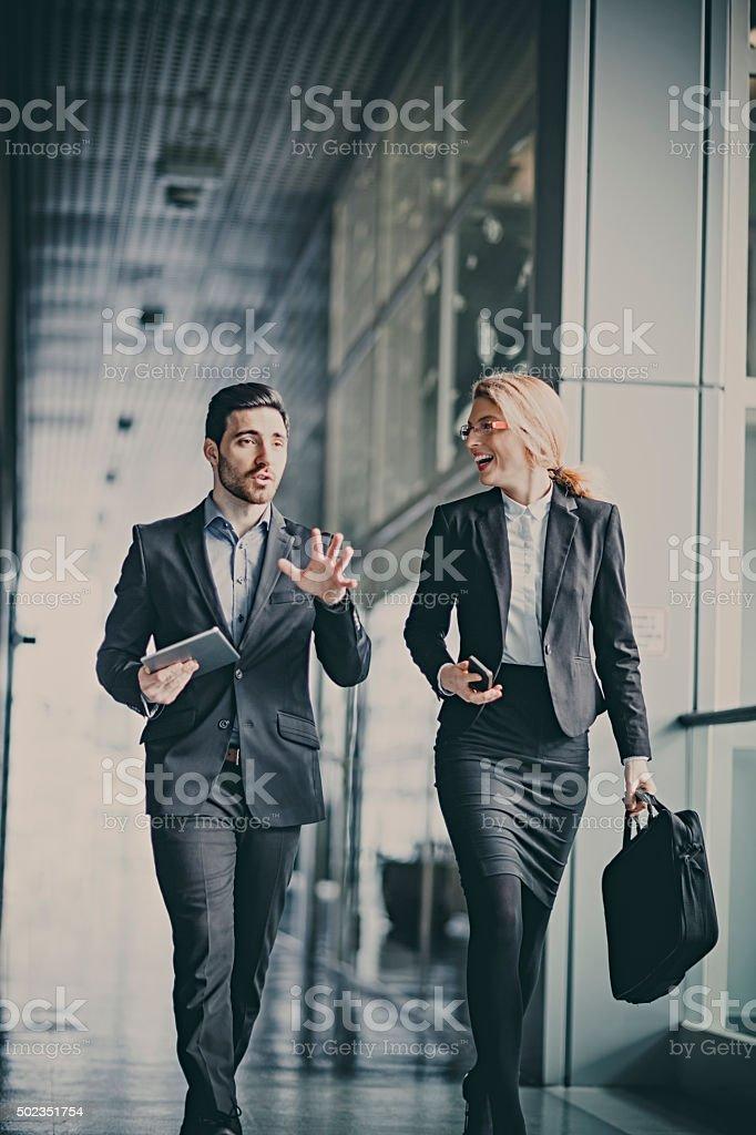 Businessmen talking in office hallway stock photo